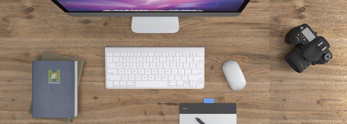scrivania con mac tastiera e penna